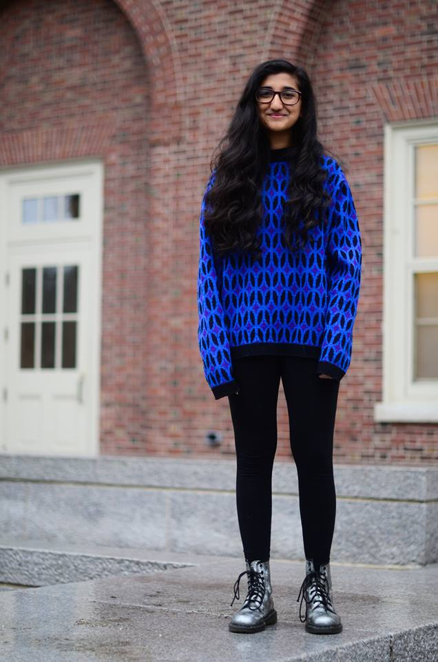 Sara from Phillips Academy Andover wears a black and vibrant blue pattern long sleeve sweater over black leggings tucked into metalic silver boots