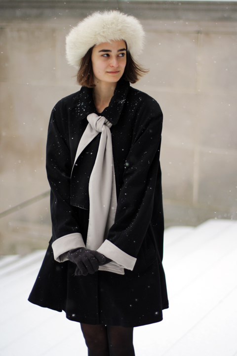 Harvard  - Anna Roth wearing a white fur hat and a black coat with gray lining