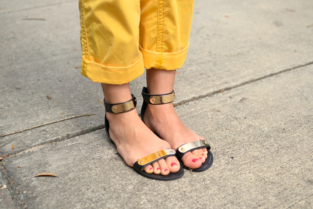Yellow cuffed khaki pants and golden band gladiator sandals