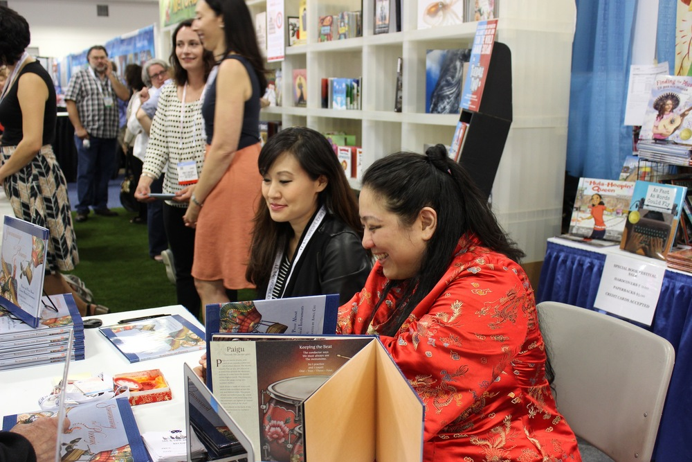 Me and Emily Jiang signing copies of our books at the Lee & Low Books Booth.