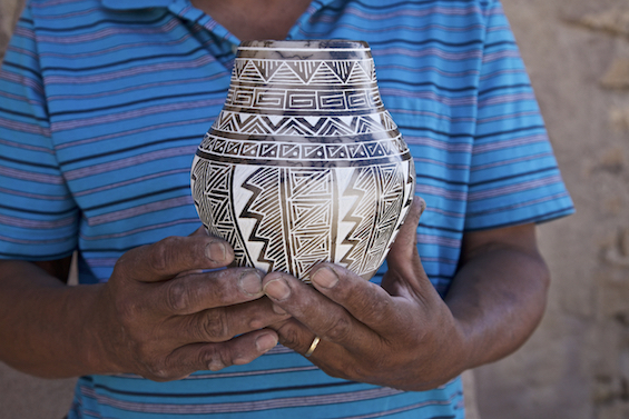 Hands of Acoma potter Gary Lous with our new horsehair pot.