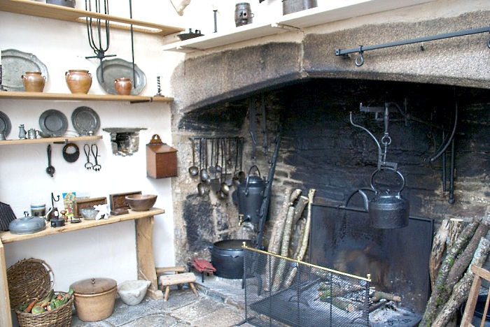 A 16th Century Tudor manor kitchen, courtesy of Home Things Past. The oversized hearth served as a multitasking feature, used for cooking, roasting, heating.