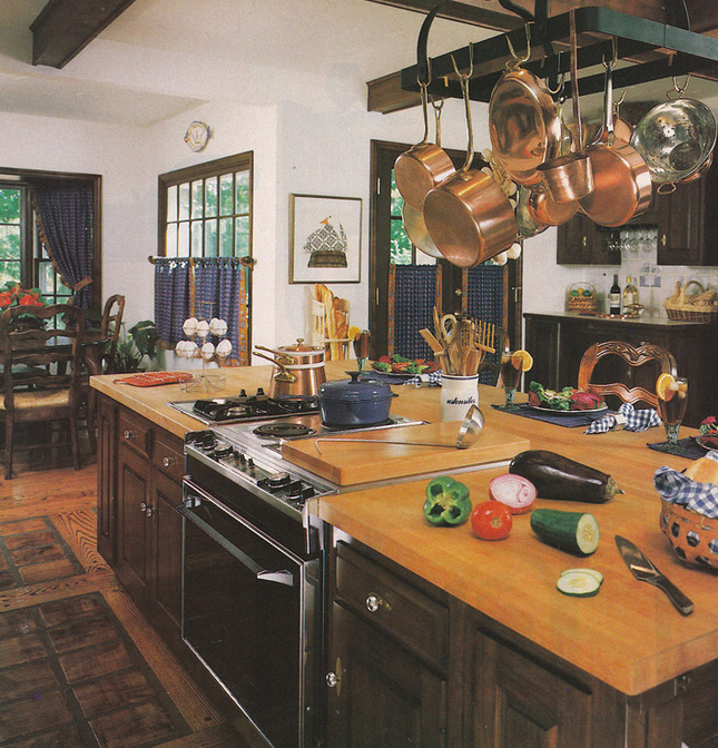 A kitchen from the 1980's, where fitted appliances, large kitchen islands, and new technologies (like the food processor and the trash compactor) dominated the design of the day. Courtesy of Vintage Goodness.