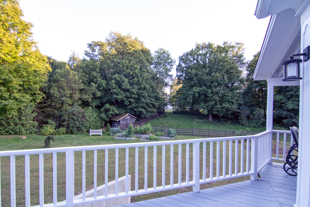 Deck overlooks back yard and young edible gardens