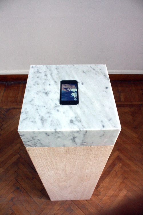 Proposal for a Romantic Sculpture, 2012, Video embedded in a sculpture. Video: 5 min. loop on iPod/iPhone, commissioned tattoo of song title 'ne me quitte pas' by Jacques Brel. Sculpture: 29 x 29 x 100 cm, marble and wood (Photo: GANZEER).