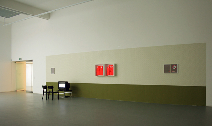 Safety Zoom, 2008-09, video installation 7 min. 13 sec., wall paint, wallpaper, life jackets, painted plywood, photographic paper collage. DV - color, sound, loop. Installation view, Bonner Kunstverein, Bonn, Germany.  WATCH HERE