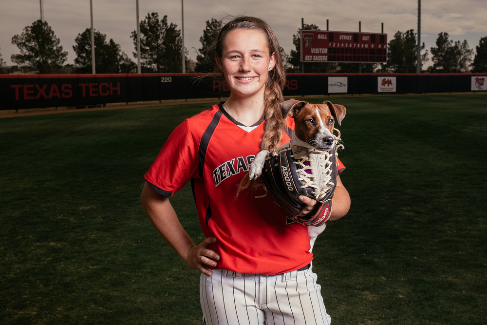 A Texas Tech softball player posing with her dog for social media promotion inviting people to bring their dogs to the next game.
