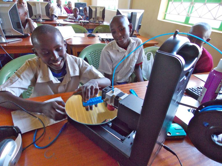 A student at Kenya Connect watches with delight as a project he designed emerges from the 3D printer. He and his classmates are participating in Level Up Village's Global Inventors course.