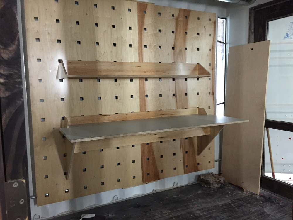 First two pegboard wall panels, a desktop and a wide shelf installed in an office during the final assembly of the WELD SuperCube in Dallas prior to shipment to Nashville.