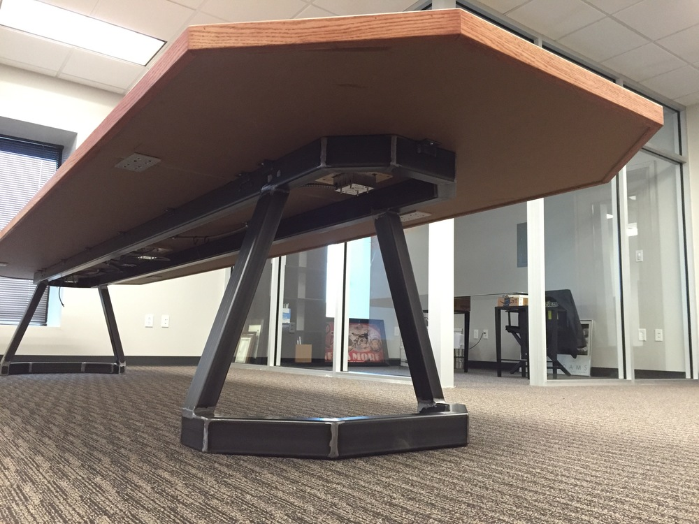 "Custom 2""x3"" steel tube base provides clearance for chairs with arms, and it hides the power harness for the built-in power outlets"