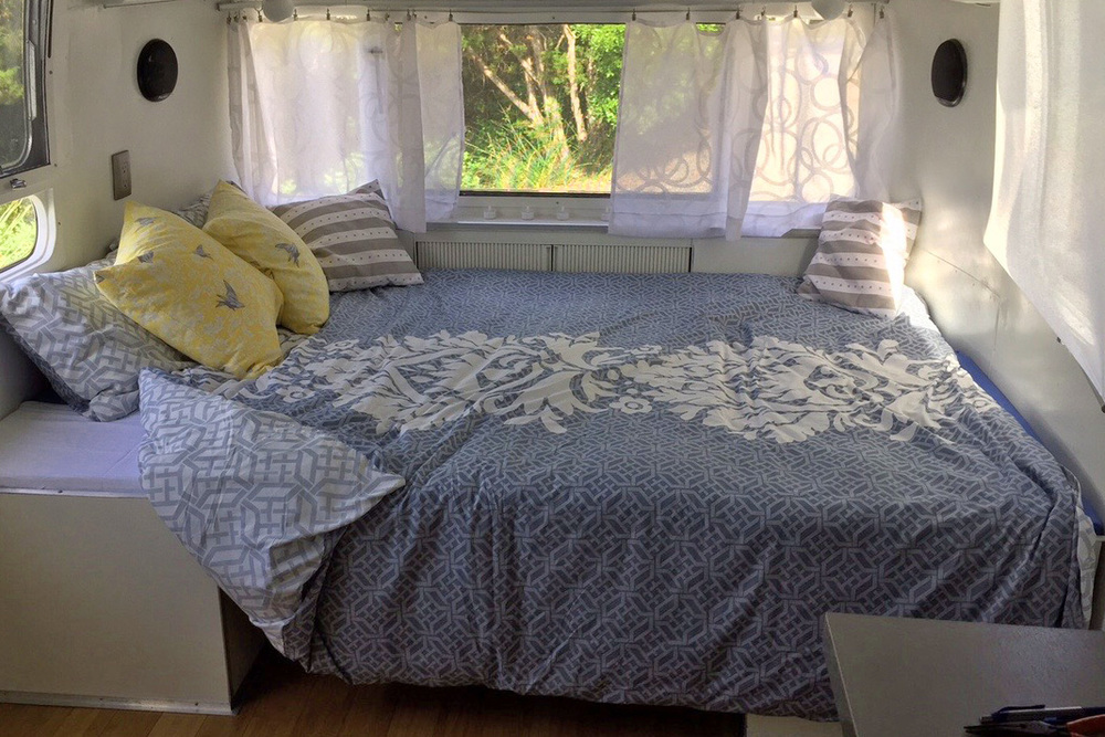 The bed made up, with views out the high Vista windows