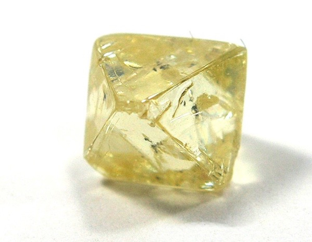 A rough, uncut yellow diamond in the octahedral form