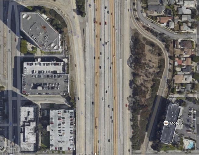 Including on- and off-ramps, Highway 405 cuts a 28-lane gash through Los Angeles.  Soaring high in the air and creating a dark, empty space beneath it, the 405 easily provides a sufficiently vast urban chasm to encourage different types of development on either side of it. (Google Maps)