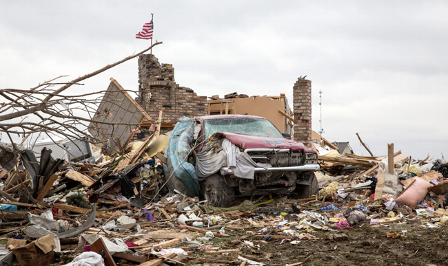 A devastated truck sits in front of a ruined home in Washington.