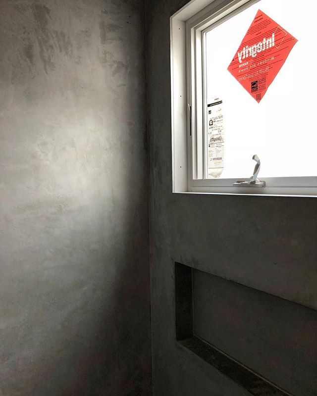Concrete micro topping, oversized shower niches and Marvin windows. A winning combo in our book.