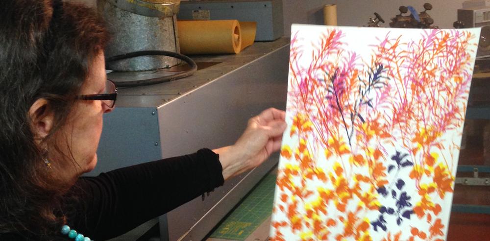 Artist & Co-op member Cynthia Gehrie examines a screen print in progress