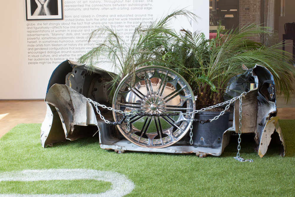Jordan Weber. Body Snatchers, 2016. Police car, chrome rims, field turf, hyperaccumulator plants, books.