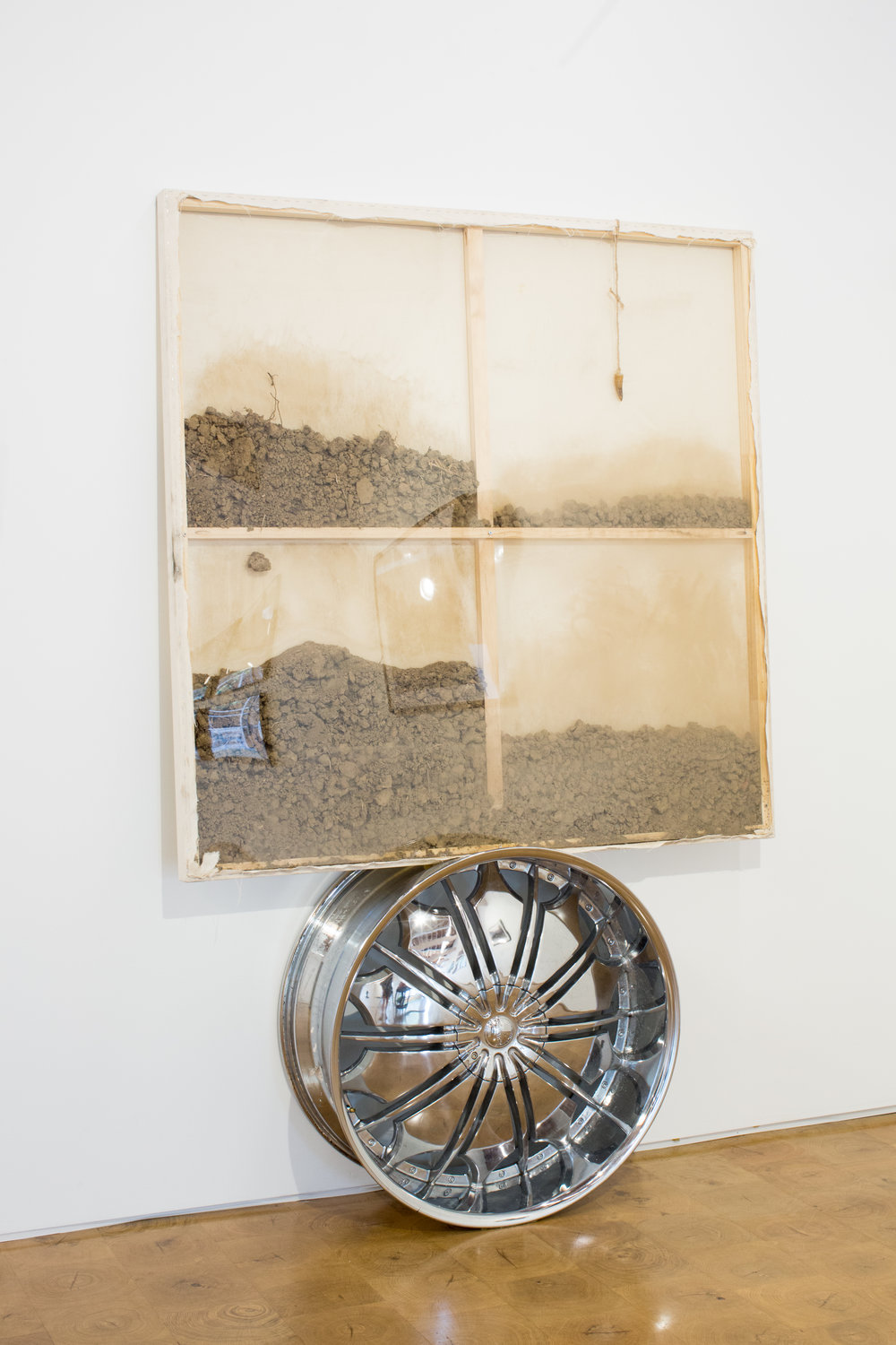 Jordan Weber.  Untitled , 2017.  Giganotosaurus tooth, chrome rim, canvas, and soils from Bethlehem, Palestine; Malcolm X Birthsite, Omaha, NE; and Ferguson, MO.