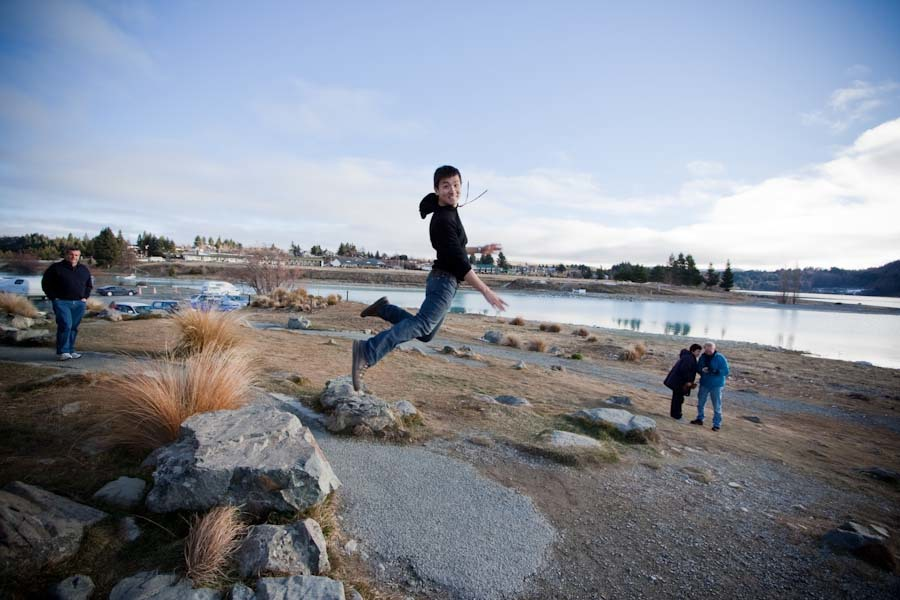 jump! at lake tekapo, new zealand south island. circa june 2009.