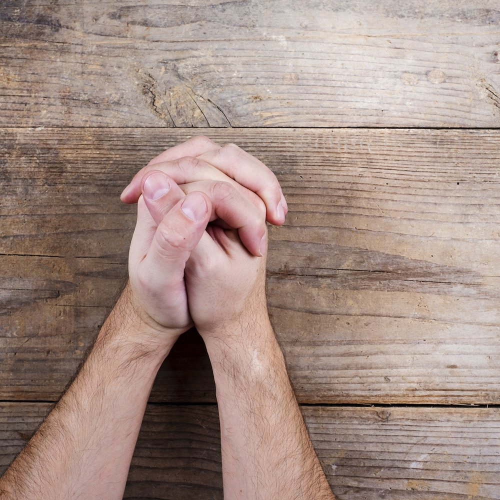 graphicstock-hands-of-praying-young-man-on-a-wooden-desk-background_SAuw5rTZ-.jpg