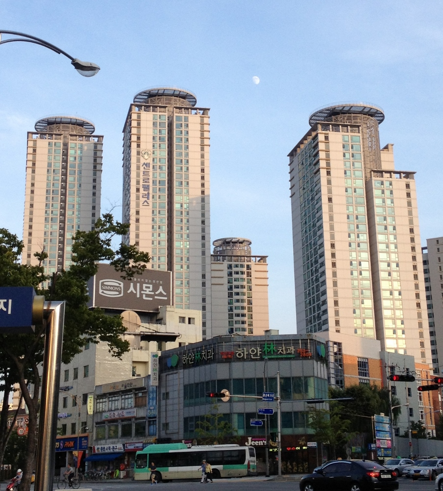 Tall dwellings near downtown, with the early evening moon in the sky
