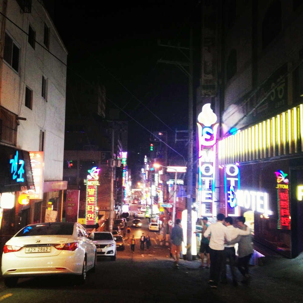 A few drunk guys arm-in-arm enjoying the Chuseok festivities around the neon-lit streets of Hadan