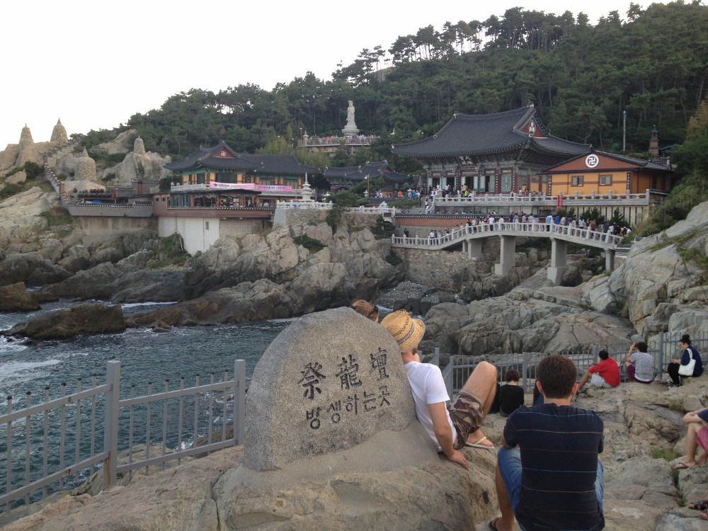 People chilling on rocks enjoying the temple view