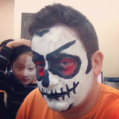 My zombie-skeleton-joker face, getting photobombed by a young student (not one of mine)