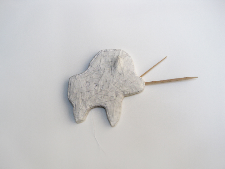 "Woolly Rhino Mummy Cookie,  2011. Cut-and-pasted handmade Japanese mending paper, pumpkin seed, cotton thread, archival corrugated cardboard. 6 7/8"" x 5 3/4"" x 3/8"""