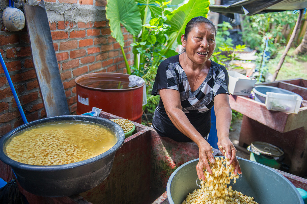 Picture of a woman rinsing corn for tamales in El Salvador by Dawn Deeks nonprofit photography