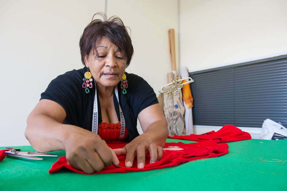 A seamstress mends costumes for an upcoming production.