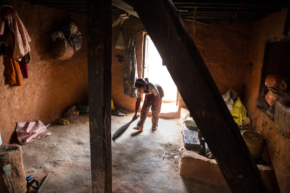 Ganga cleans the main floor of the house. Her parents sleep on a mat in the corner with their youngest daughter, Sabita. It's also where they keep the chickens.