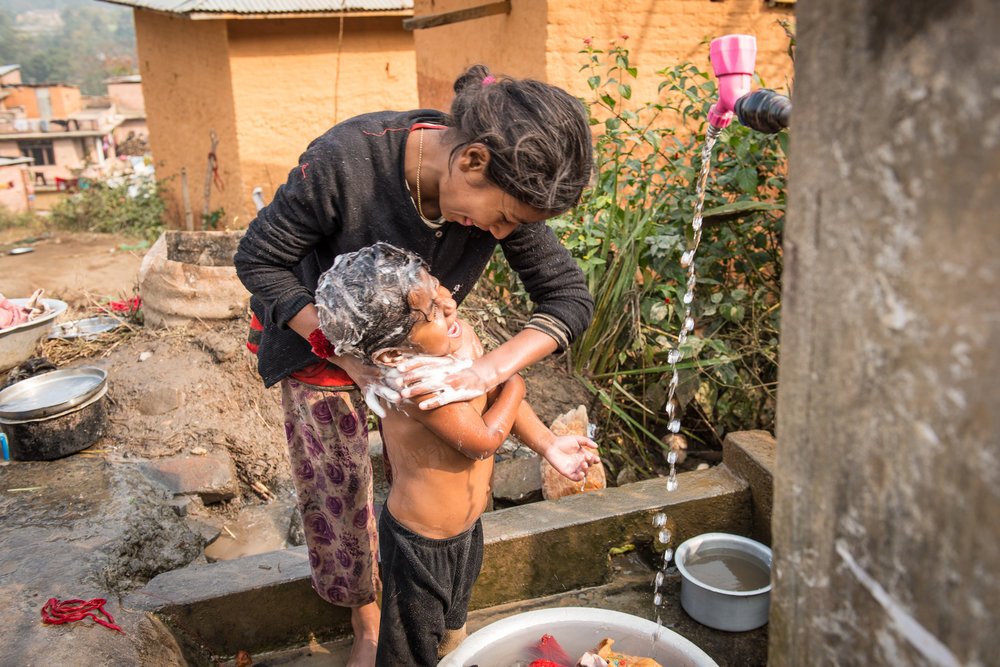 Ganga gives Rasu a bath.With their mother out working every day, the household responsibilities often fall to Ganga and her older sister Jamuna.