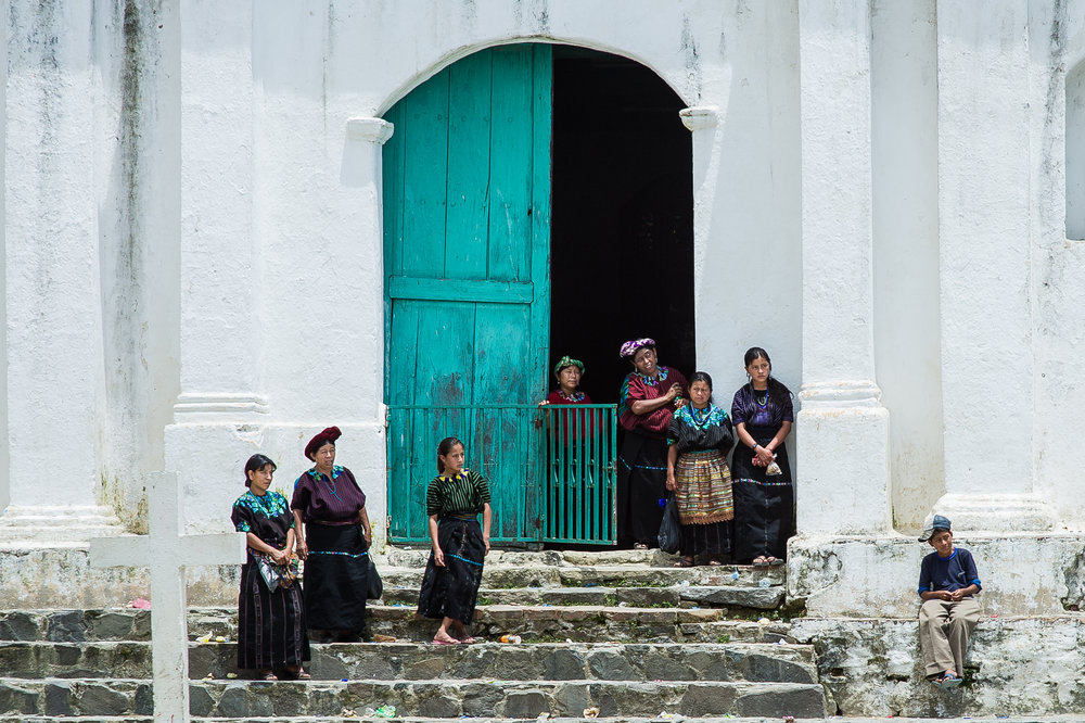 Women and children in traditional dress gather near the church in Santa Cruz's town square.