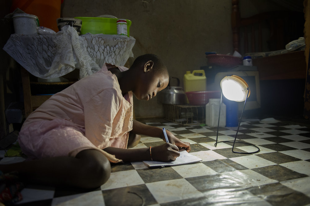 Jane's granddaughter uses a portable solar lantern  to study.