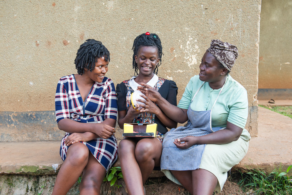 Brenda and Lillian show Josephine a portable solar lantern.