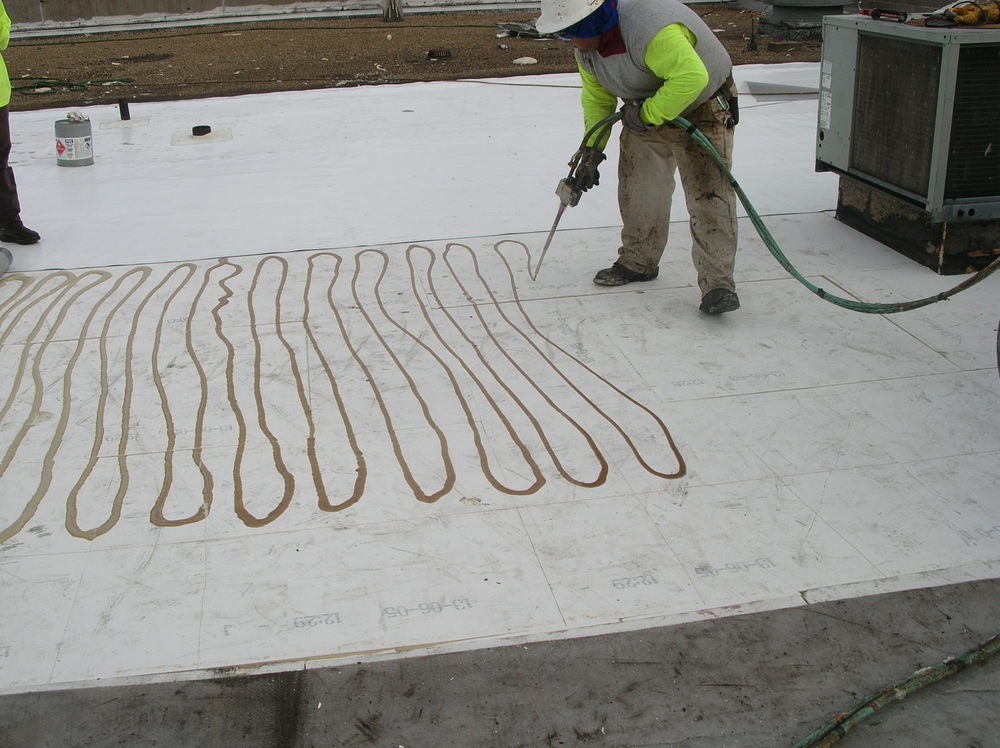 Applying adhesive to the cover board before setting a PVC roofing membrane