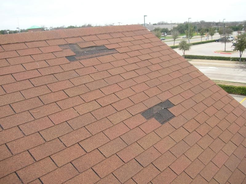 Wind-damaged 3-tab asphalt shingle roof.
