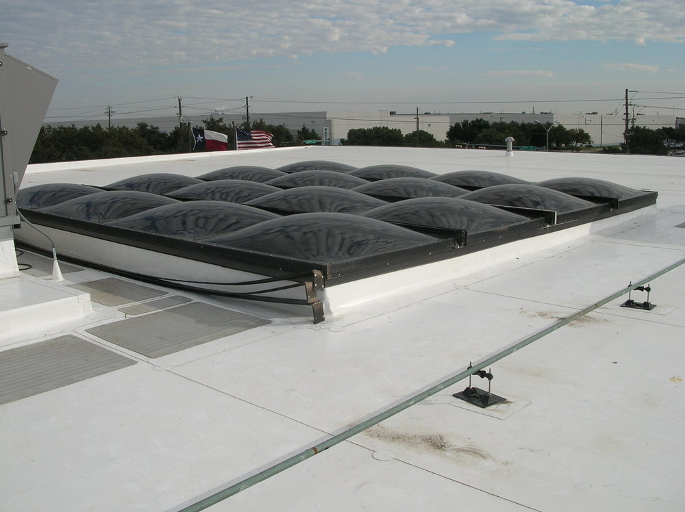 Skylight system with acrylic domes and aluminum framing.