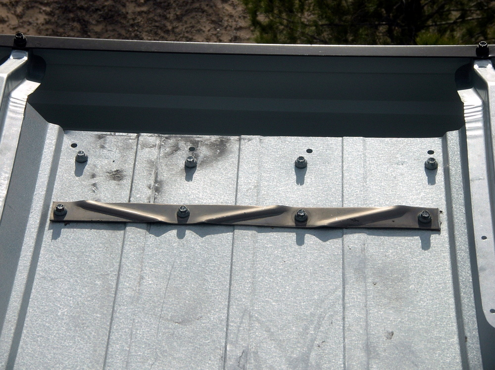 Fasteners at the gutter edge of a metal panel roof .