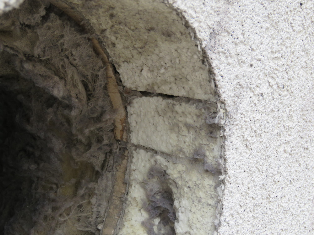 An exhaust duct hole through the EIFS cladding reveals the constituent EIFS components.