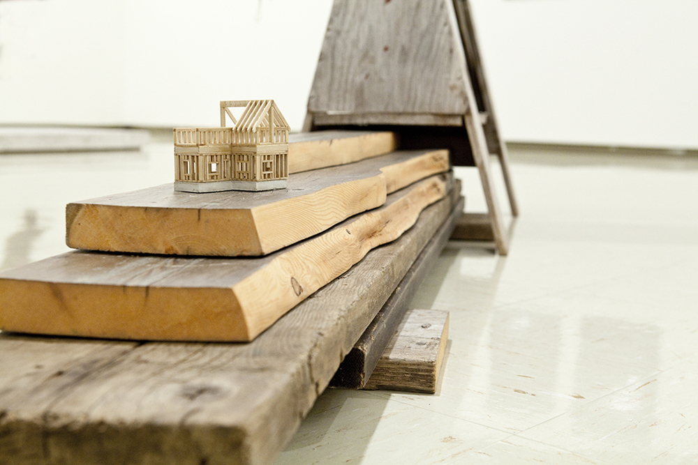 "I own five wooden senses, and a sixth like water,  2012 Used wooden planks, hand-milled poplar and pine, cement, plywood, cedar shingles, and twine. Detail view of larger installation House size: 4"" x 3"" x 2"""