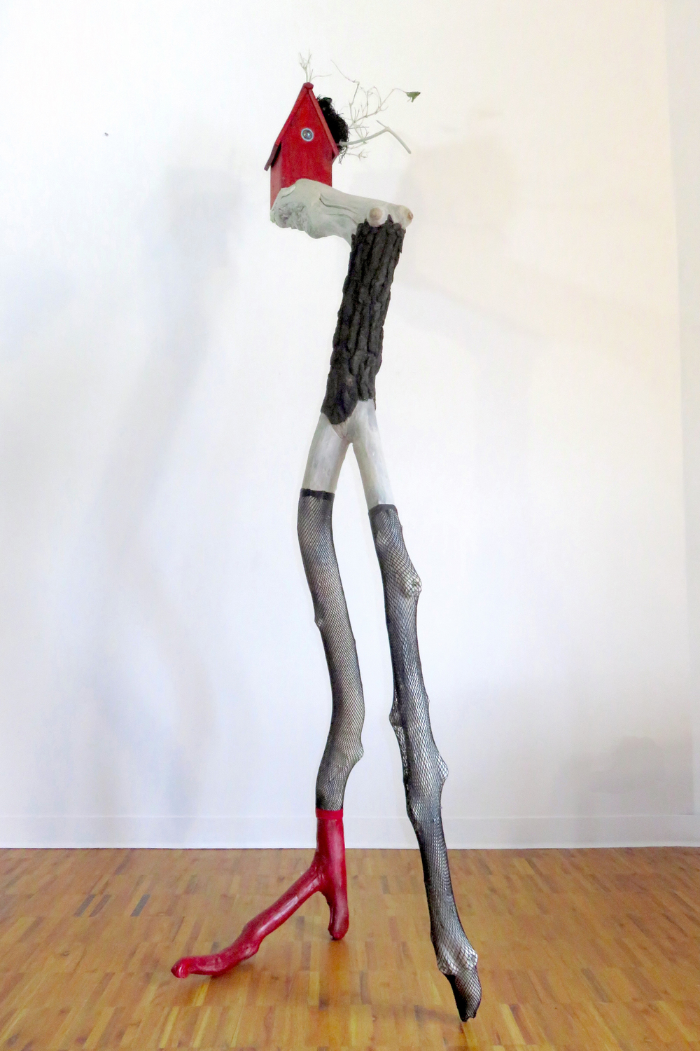 "The Fascinator,  2015 Tree limbs, wood house, LED light, glass, bird's nest, nylon stockings, acrylic paints, wood stain 96"" x 30"" x 32"""