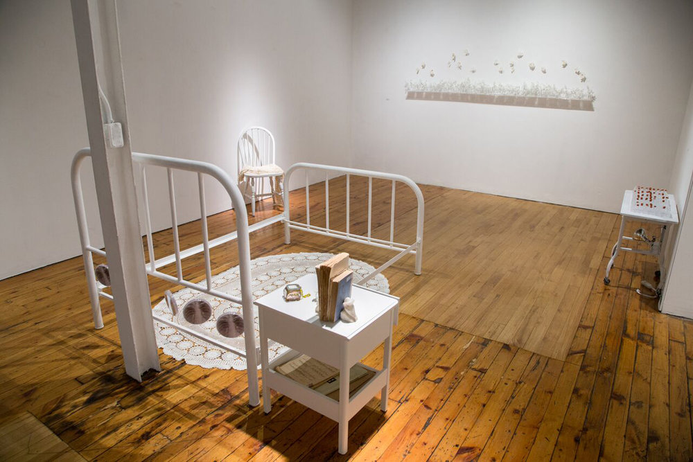 Contained  (installation),   2018 Bed, bedside table, chair, crocheted shawl by Louise while in sanitorium, her books and music piano music sheets, personal items, table cloth, petri dishes with ink drawing and X-ray of lungs with TB