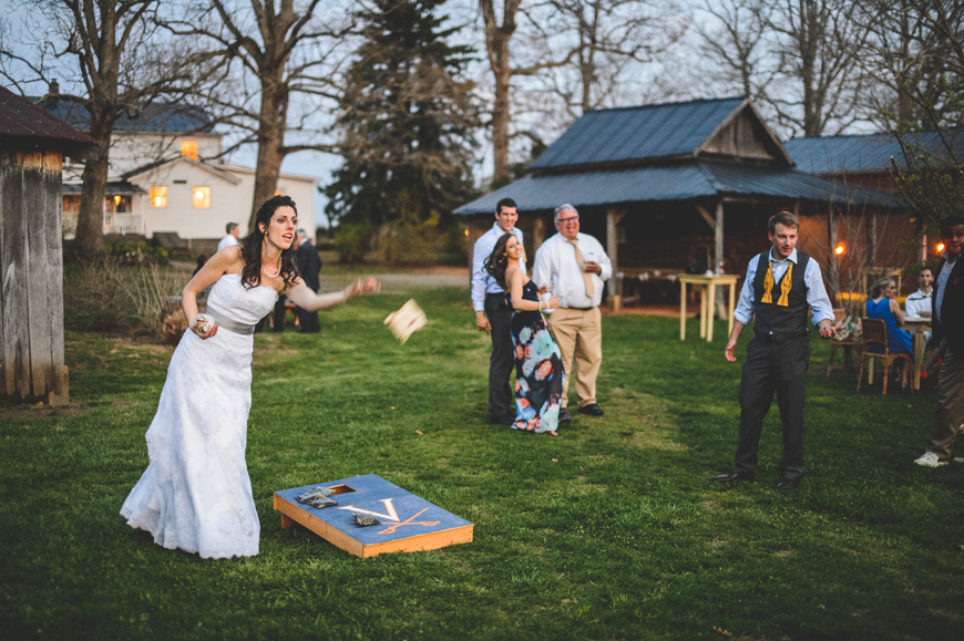 032 bride playing cornhole during wedding