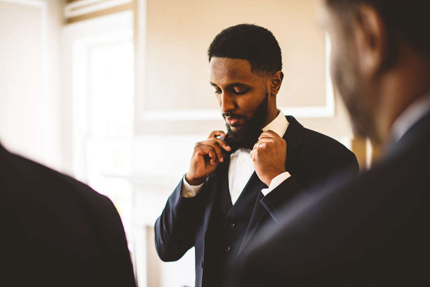 002 groom adjusts brown bow tie.jpg