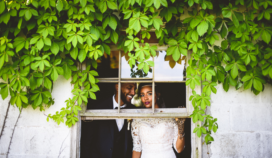 014 gorgeous bride looking out an old broken window.jpg