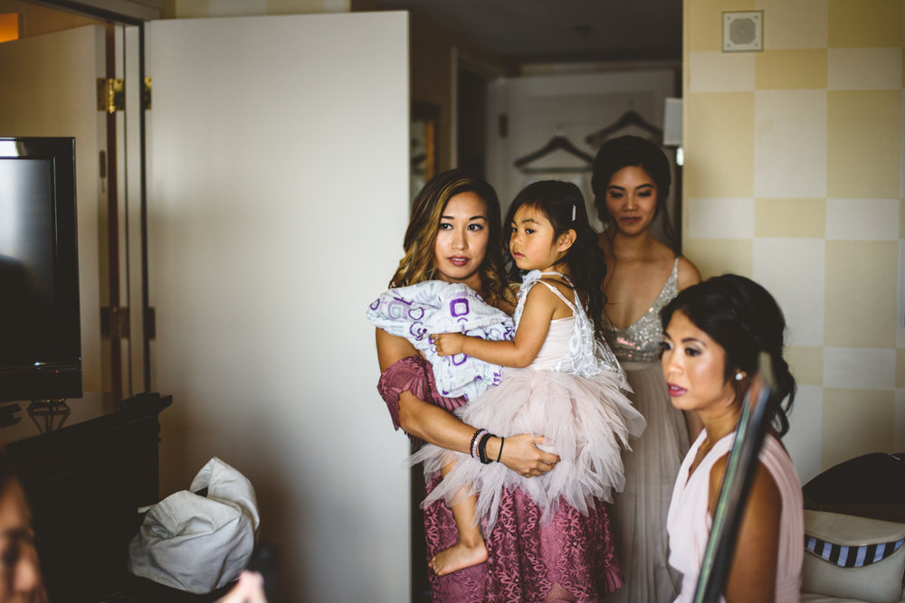 003 bridesmaid and child look at bride getting into wedding dress.jpg