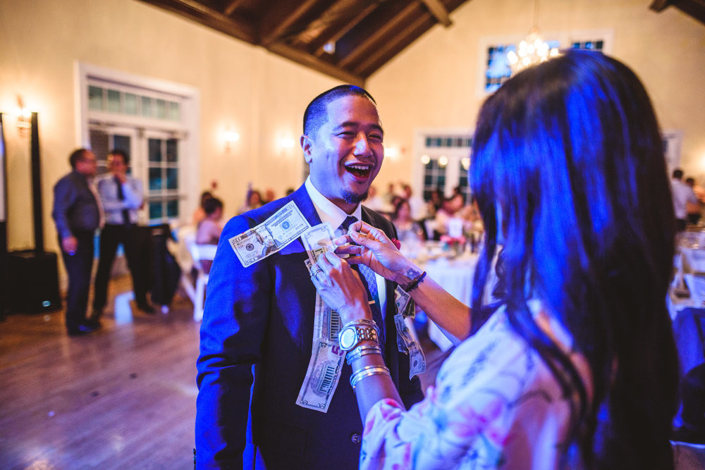 050 woman pins the groom during a filipino money dance.jpg
