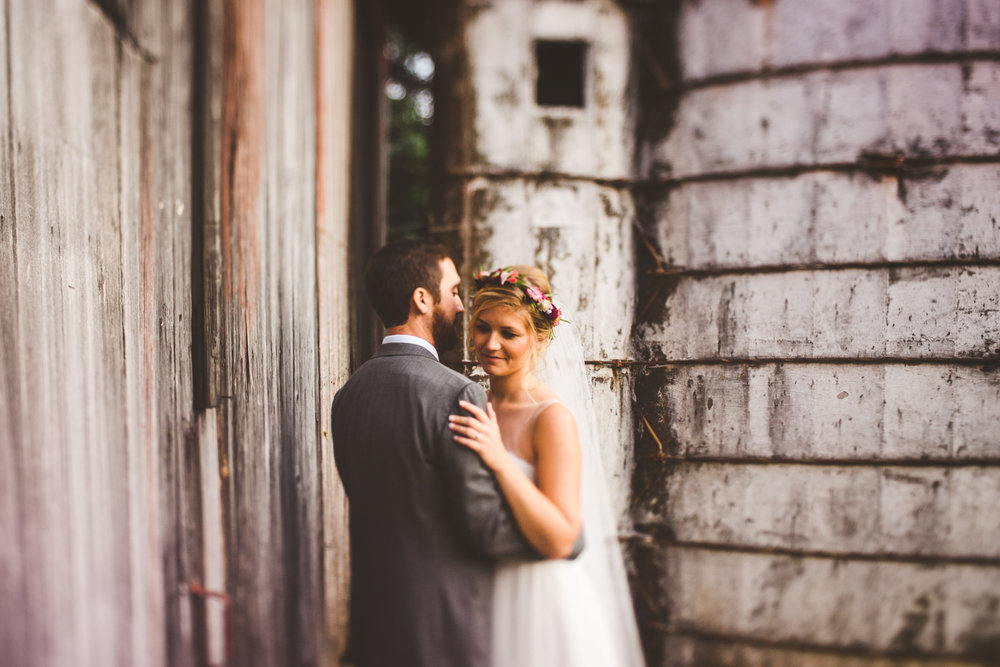 021 - freelensing bride and groom in front of barn with grain storage.jpg